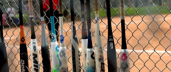 Softball bats hanging on chainlink fence.